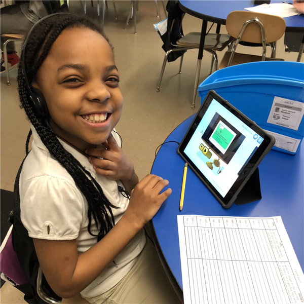 Girl student smiling while engaging in blended learning on Digital Learning Day